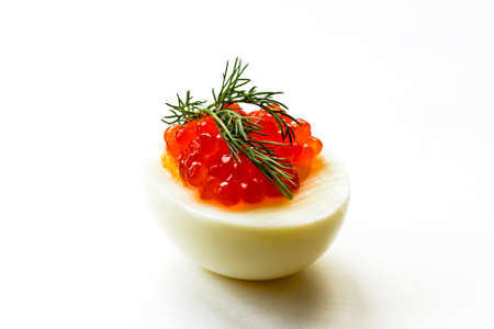 Hard-boiled sliced chicken egg half with red caviar and dill on white background. Close up. Selective focus. Copy space 写真素材