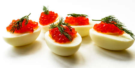 Hard-boiled sliced chicken egg halves with red caviar and dill on white background banner. Close up. Selective focus. Copy space