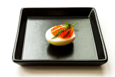 Hard-boiled sliced chicken egg half with red caviar and dill on black plate on white background. Close up. Selective focus. Copy space