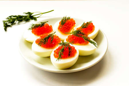 Hard-boiled sliced chicken egg halves with red caviar and dill on white plate background. Close up. Selective focus. Copy space