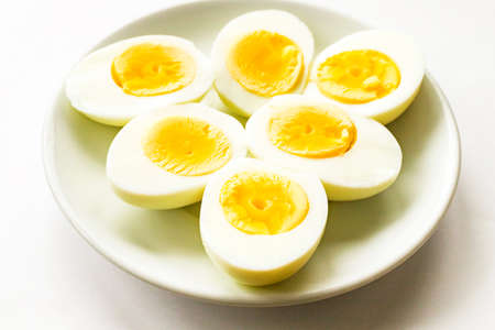 Hard-boiled sliced chicken egg halves on white plate on white background. Close up. Selective focus. Copy space 写真素材