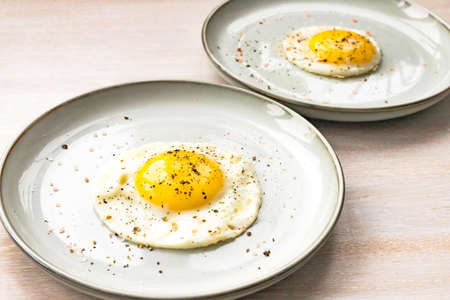 Close-up fried egg for two in plate with pepper on white wooden table background. Morning breakfast concept. Close up. Selective focus. Copy space 写真素材
