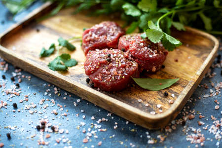 Raw meat beef steak on wooden tray, coarse pink Himalayan salt, black pepper, bay leaf, herb. Close up. Selective focus. Copy space 写真素材