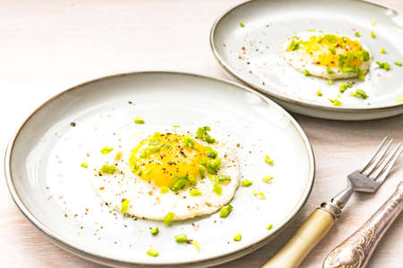 Close-up fried egg for two in plate salt, pepper, green onion on white wooden table background, fork, knife. Morning breakfast concept. Close up. Selective focus. Copy space