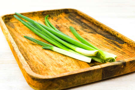 Green spring onion Scallion feathers on wooden tray on white table background. Close up. Selective focus. Copy space