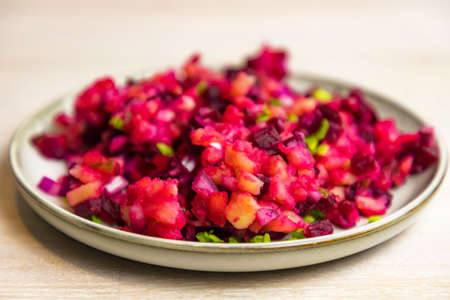 Russian Vinegret beet salad of boiled vegetables in gray white plate on white table background. Close up. Selective focus. Copy space