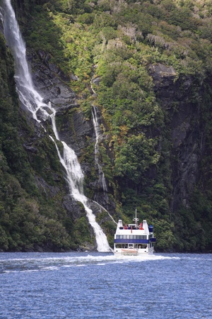 A Boat riding beside a water fall in Milford Sound in New Zealand