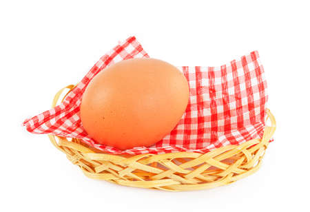 suppertime: egg in wicker basket with a checkered napkin isolated on white background