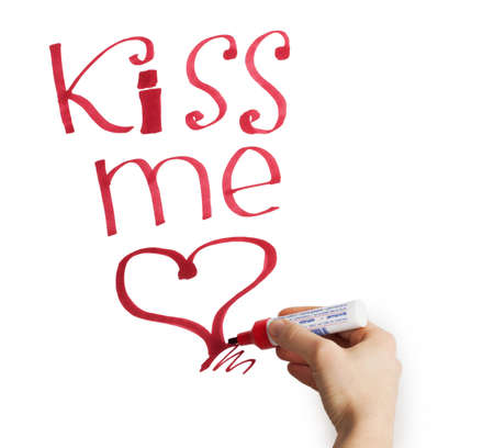 Female hand writing kiss me marker on a white background photo