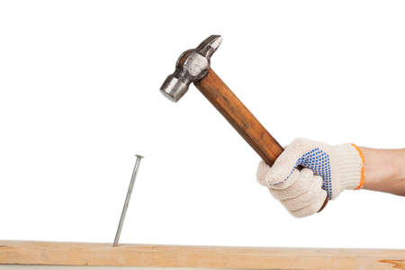 male hand in working glove hits the nail into a wooden board on the white background photo