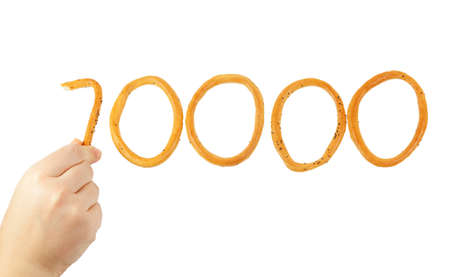 boublik: Hand puts the number of ten thousand of bagels isolated on white background Stock Photo