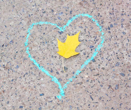 yellow leaf in the heart drawn in chalk on gray asphalt photo