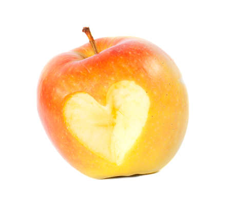 yellow apple with a carved heart isolated on white background photo