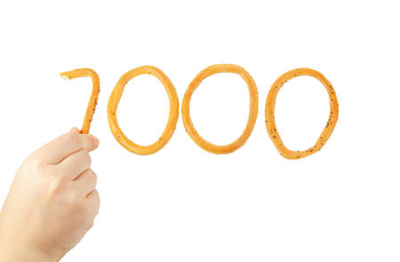 Hand puts the number one thousand of bagels isolated on white  Stock Photo