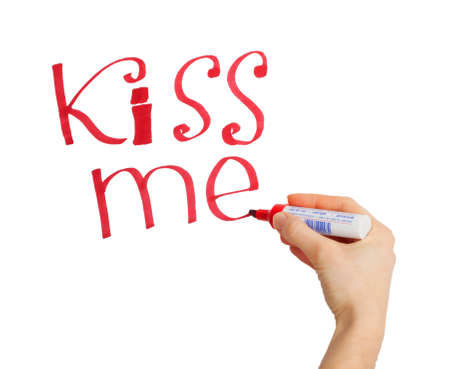 Female hand writing 'kiss me' marker on a white  photo