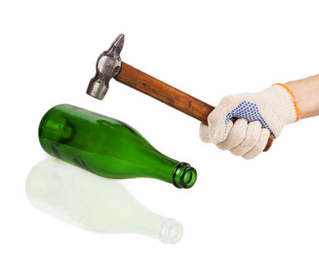 Working hand in glove holding a hammer over a green bottle isolated on white  photo