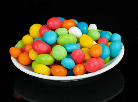 colored candies in white saucer isolated on black background photo