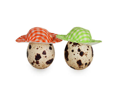two quail eggs dressed in colorful hats isolated on white background photo