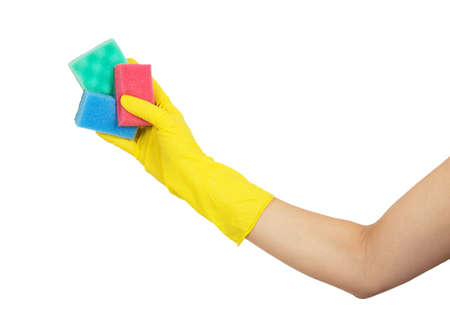 Female hand in yellow glove holding with colorful sponges isolated on white background photo