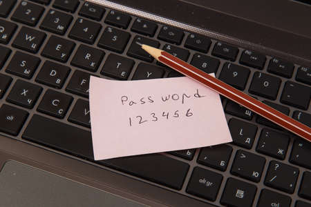 Sticky note with password and pencil on black laptop photo