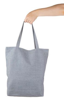 Mano femenina que sostiene una bolsa de compras textil gris aislado en el fondo blanco