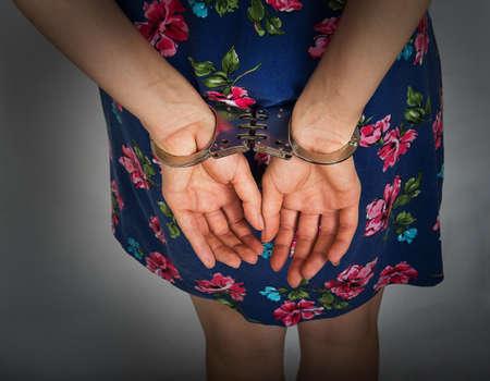 esclavo: Manos femeninas en las esposas sobre un fondo gris