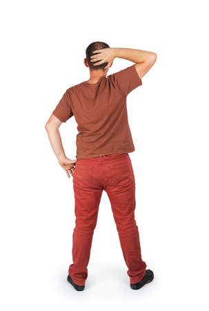 Back view of a confused young casual man with his hand on the back of his head isolated on white background photo