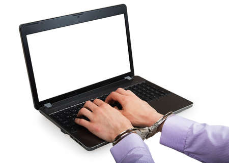 Hands in handcuffs on a laptop with white screen isolated on a white background photo
