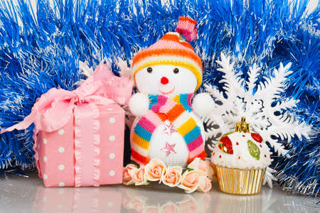 Snowman with pink gift box and white snowflakes on a background of blue garland photo