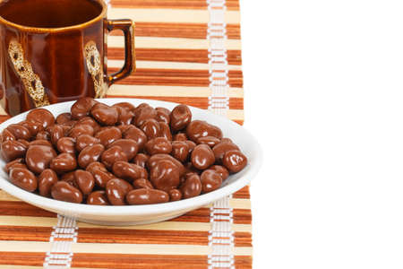 dragee: Chocolate dragees in a white saucer on a bamboo mat on a white background