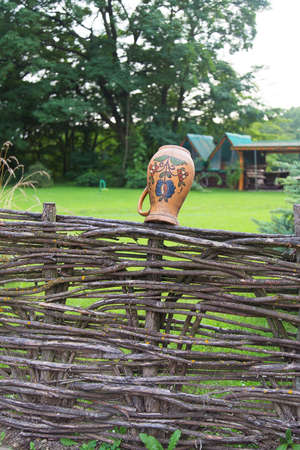 Clay jug on fence, a village tradition in Ukraine photo