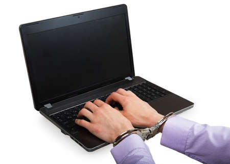 Hands in handcuffs on a laptop isolated on a white background photo