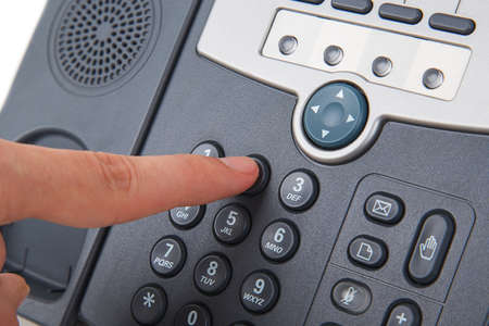 woman dialing phone number: office black telephone with hand isolated on white Stock Photo