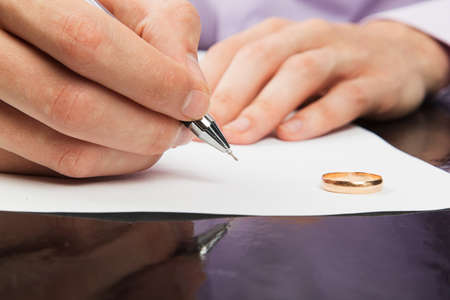 Closeup of male hand signing divorce papers