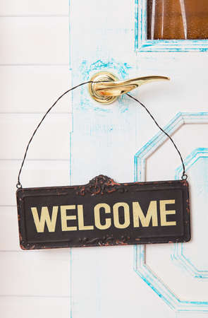 old sign: Wooden welcome sign on white door