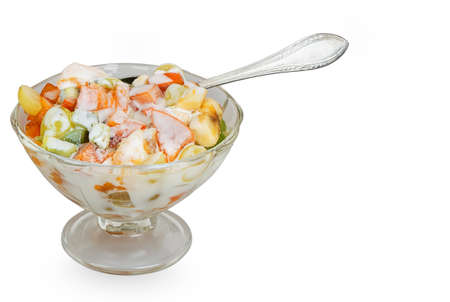 Fruit salad in the glass bowl with spoon isolated on white background photo