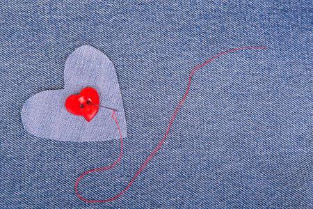 hilo rojo: Botón rojo en forma de corazón con la aguja y el hilo rojo en tela de mezclilla