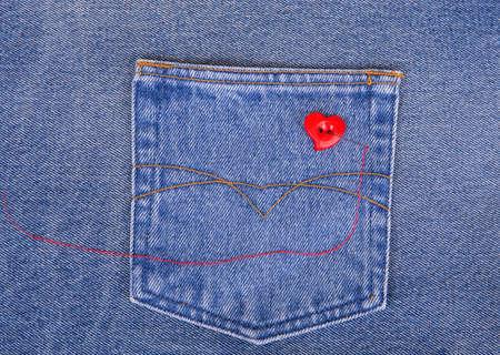hilo rojo: Bot�n rojo en forma de coraz�n con la aguja y el hilo rojo en tela de mezclilla