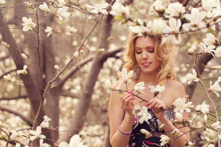 white blossom: Beauty smiling woman near white magnolia in botanical garden Stock Photo