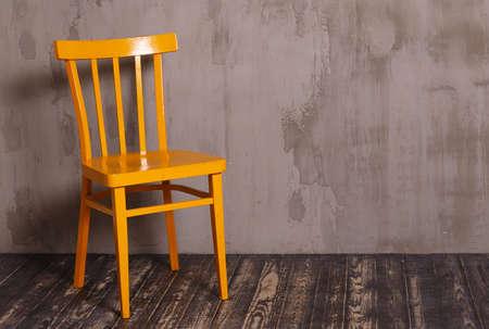silla de madera: Yellow wooden chair in nterior room with gray decorative plaster wall and dark wooden floor Foto de archivo