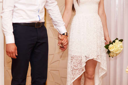 registry: Bride and groom holding hands in a registry office Stock Photo