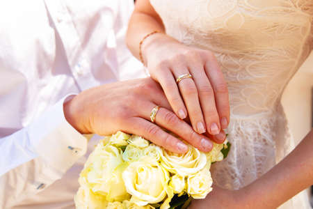 hand holding flower: Hands and rings on wedding bouquet close up Stock Photo