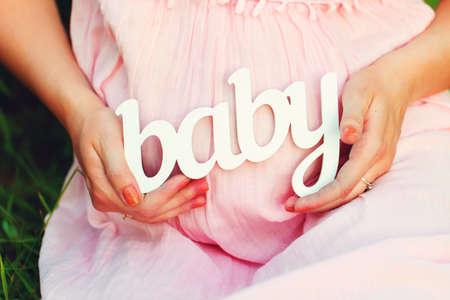 """vientre femenino: Etiqueta de """"Baby"""" en las manos de una mujer embarazada al aire libre"""