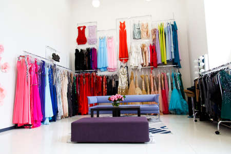 woman in red dress: Evening dresses on hangers in store