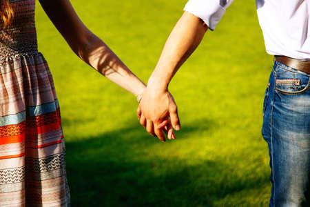 manos agarrando: Pareja de la mano en el fondo de la hierba verde Foto de archivo