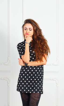 offended: Young offended woman in black dress in the studio