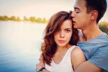 7b2590f8d  65536917 - Hombre joven hermoso que besa a su novia cerca del río