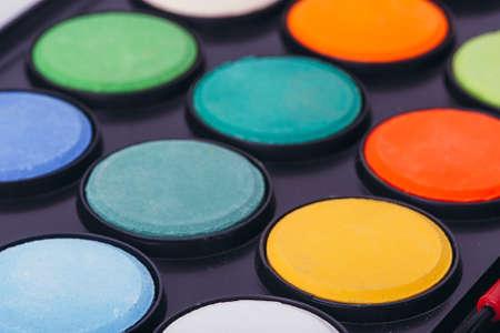 Paint watercolors pallet close up on black