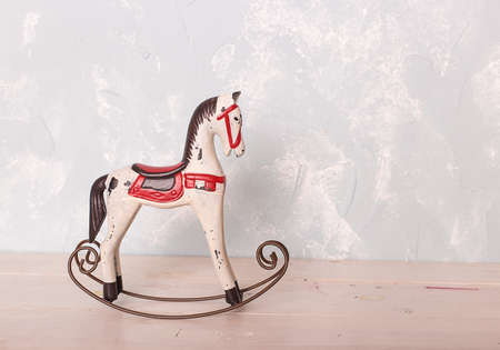 toy rocking white horse on the wooden floor against the backdrop of a blue wall