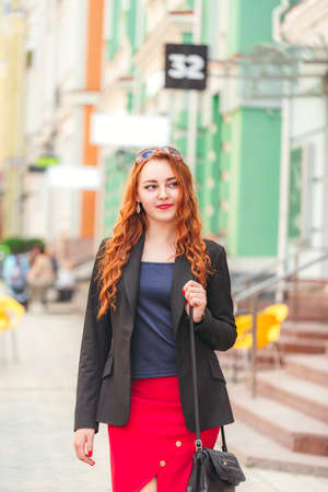 sidewalk talk: Young red-haired business woman walking down the street, looks in the frame